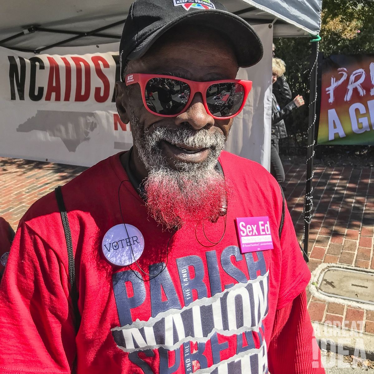 Attendee at Greensboro Pride wears A Great Idea voter pins